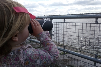Child looking through binoculars at Walthamstow Wetlands