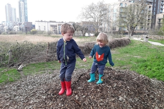 Children jumping on bark chippings and leaves