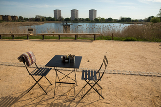Outdoor seating at the Coal House Cafe, Woodberry Wetlands. Two chairs and a table.