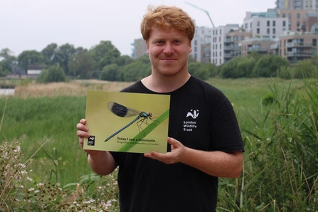London Wildlife Trust staff member holds a copy of the guide book